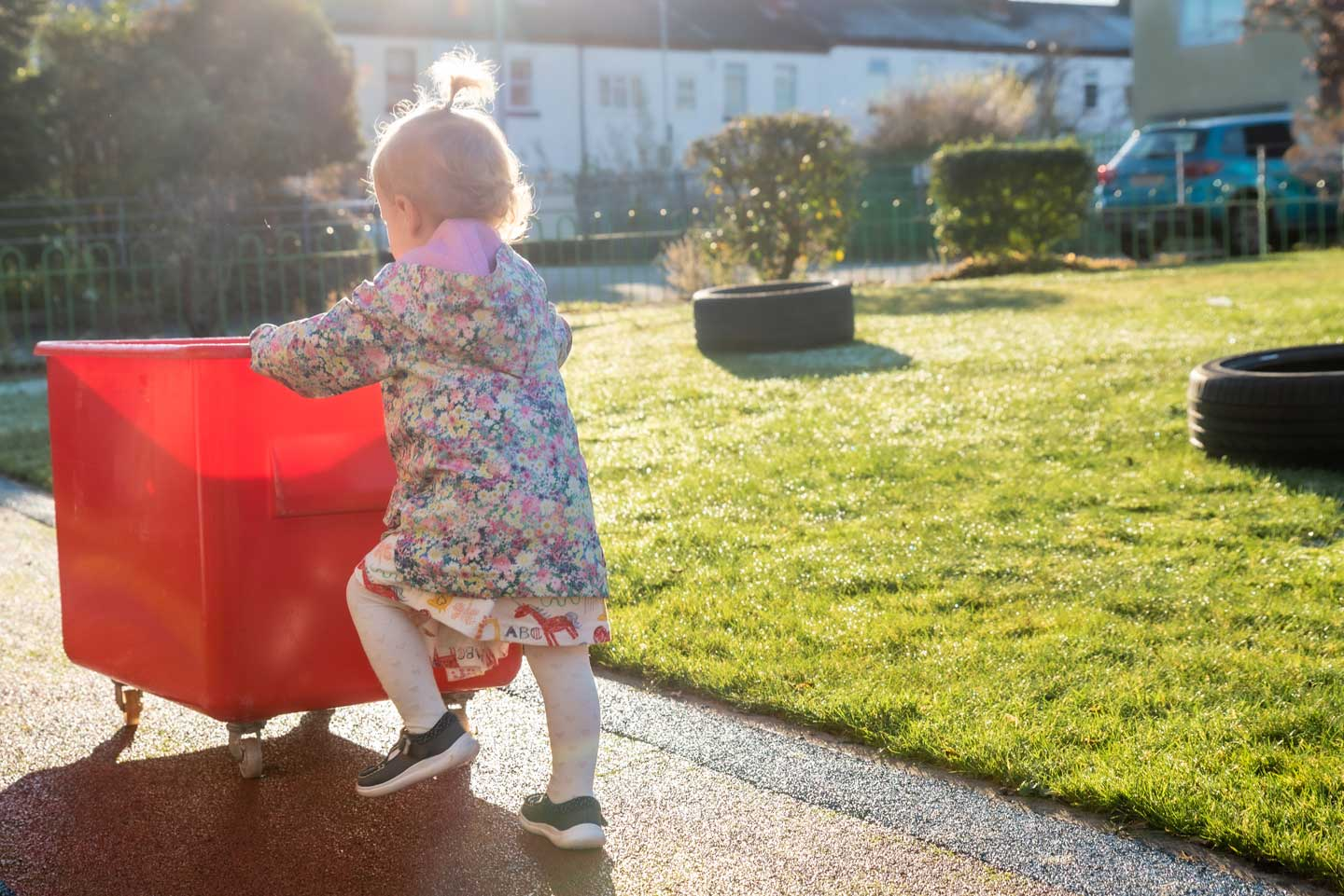 toddler pushing red trolley at baby stay and play