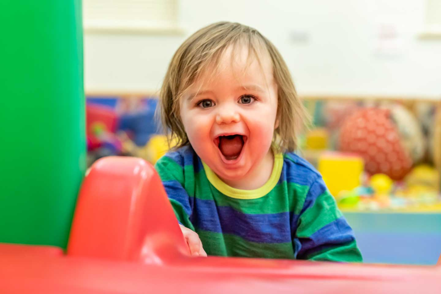 Open mouthed lttle boy exploring and learning in soft play area
