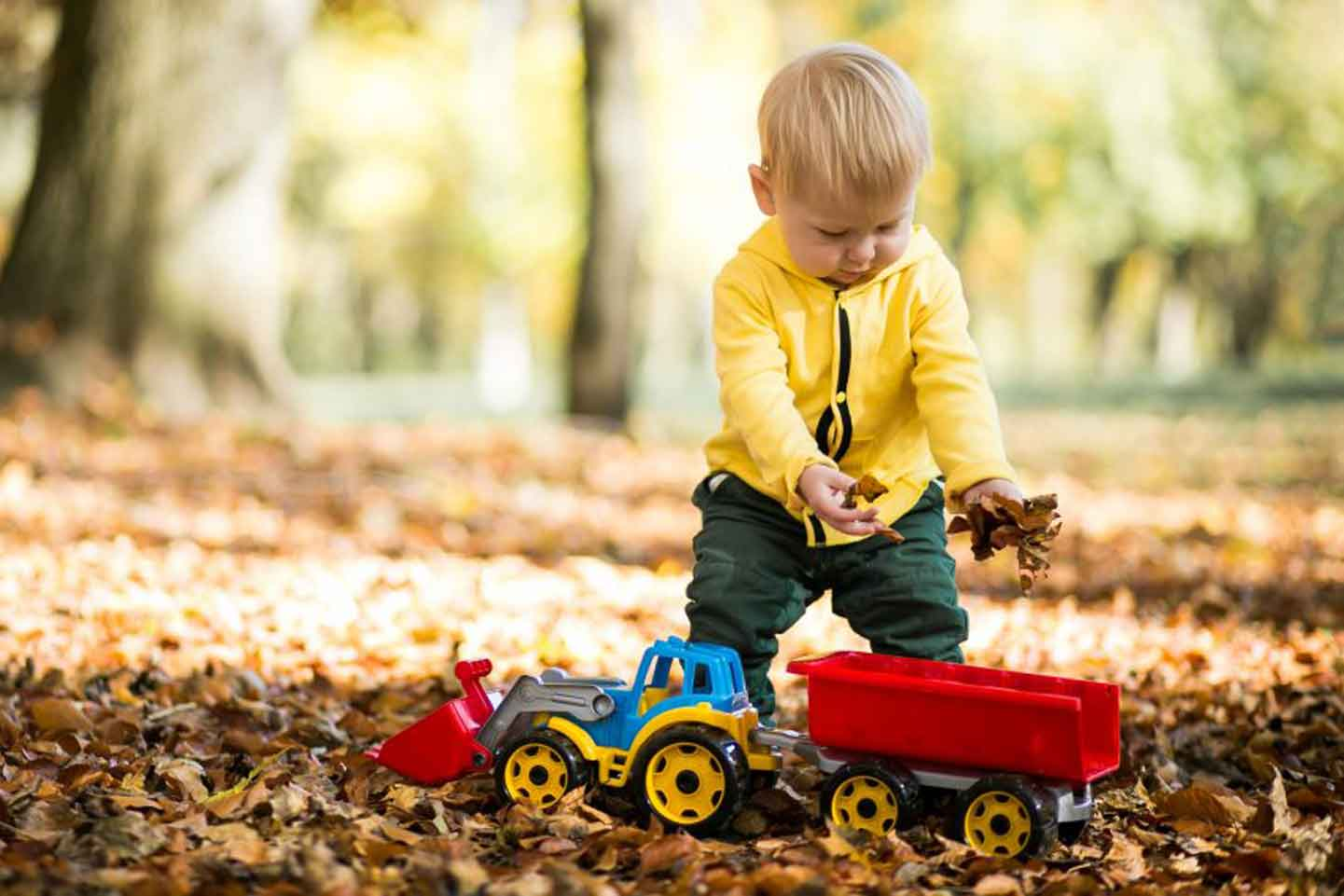 Little boy placing bark chipping in toy tractor in outdoor learning experience